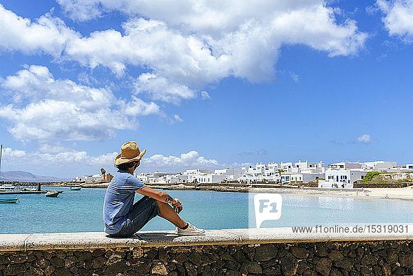 Man sitting on wall looking towards Caleta de Sebo  La Graciosa  Canary Islands  Spain