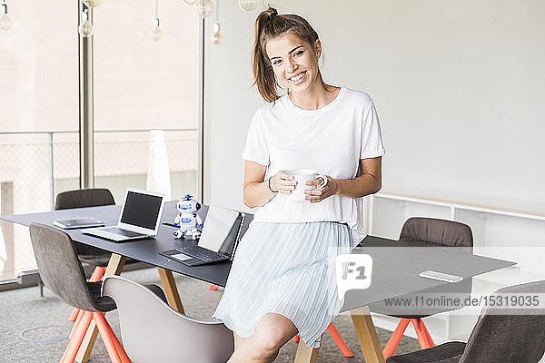 Porträt einer lächelnden jungen Geschäftsfrau mit Kaffeepause im Büro