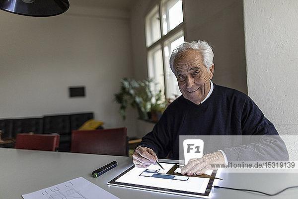 Porträt eines lächelnden älteren Mannes mit Tablett mit Architekturplan