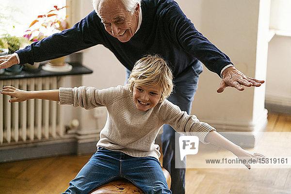 Glücklicher Großvater und Enkel spielen zu Hause mit Bock