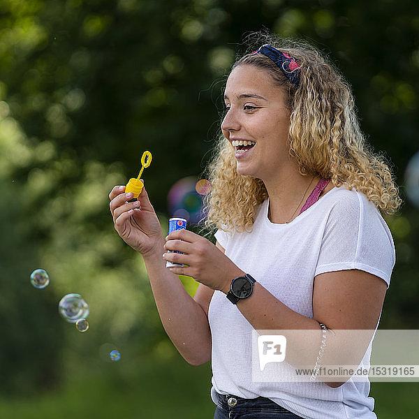 Lachende blonde Frau macht Seifenblasen
