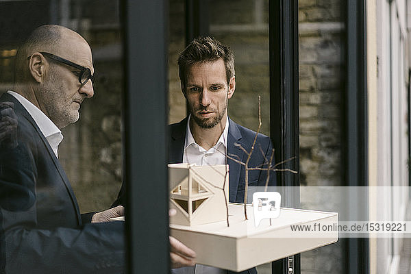 Senior and mid-adult businessman with architectural model