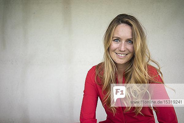 Porträt einer lächelnden Frau im roten Overall