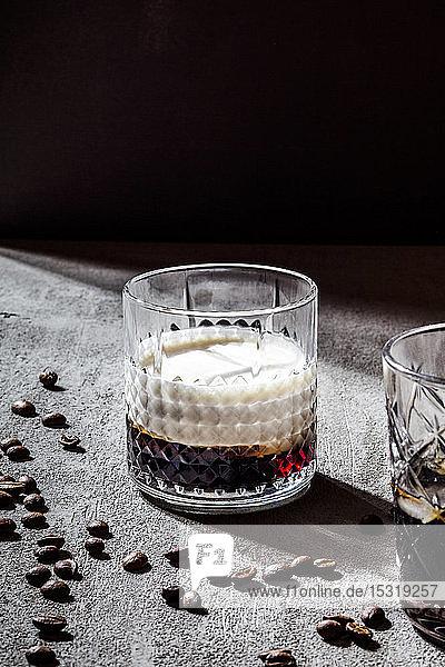 Nahaufnahme von White Russian in Glas durch geröstete Kaffeebohnen auf Betontisch