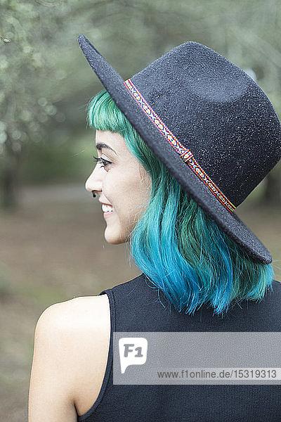 Lächelnde junge Frau mit gefärbten blauen und grünen Haaren  die an einem regnerischen Tag einen Hut trägt