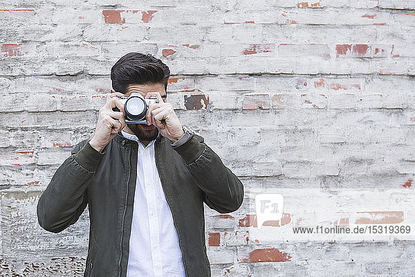 Young man taking picture with camera