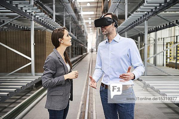 Geschäftsfrau im Gespräch mit einem Geschäftsmann mit VR-Brille in einer Fabrik