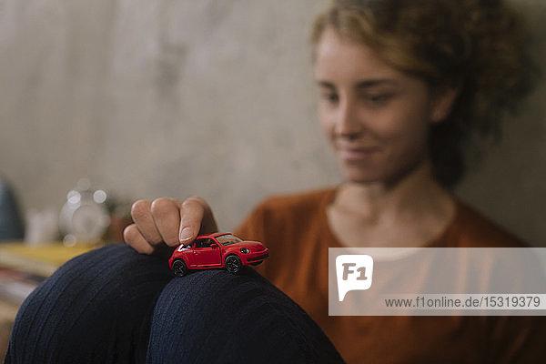 Junge Frau spielt mit rotem Spielzeugauto