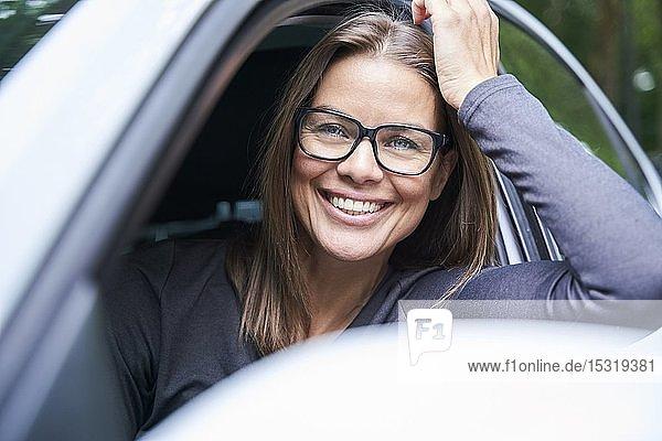Porträt einer lächelnden Frau in einem Auto