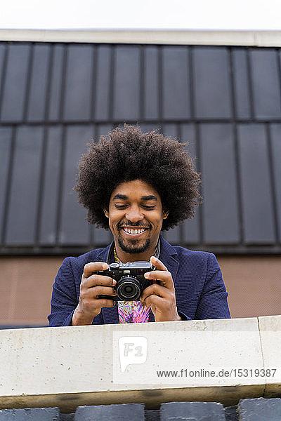 Fröhlicher stilvoller Mann schaut in die Kamera