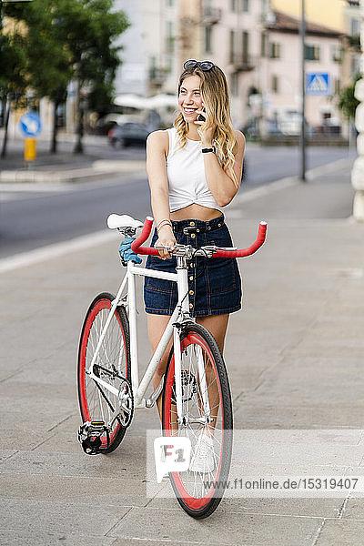 Porträt einer lächelnden jungen Frau mit Rennrad am Telefon