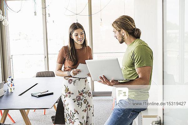 Junge Geschäftsfrau und Geschäftsmann mit Laptop im Büro
