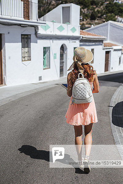 Back view of fashionable young tourist with backpack walking along the street  Frigiliana  Malaga  Spain