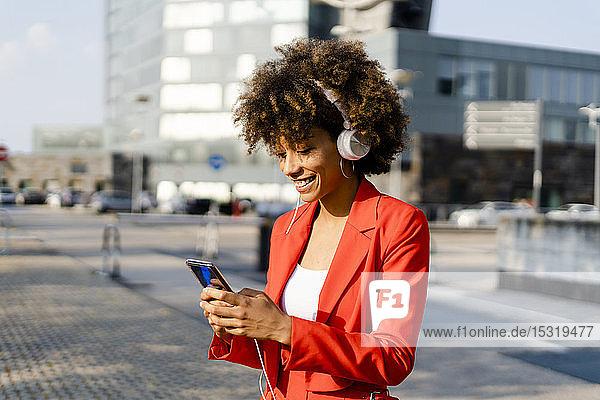 Lächelnde junge Frau mit Kopfhörern in modischem roten Hosenanzug schaut auf Smartphone