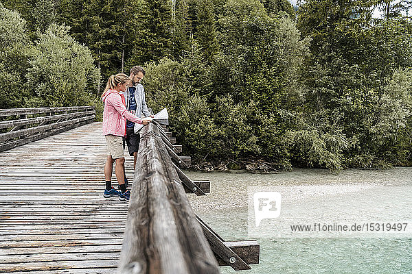 Young couple on a hiking trip reading map on wooden bridge  Vorderriss  Bavaria  Germany