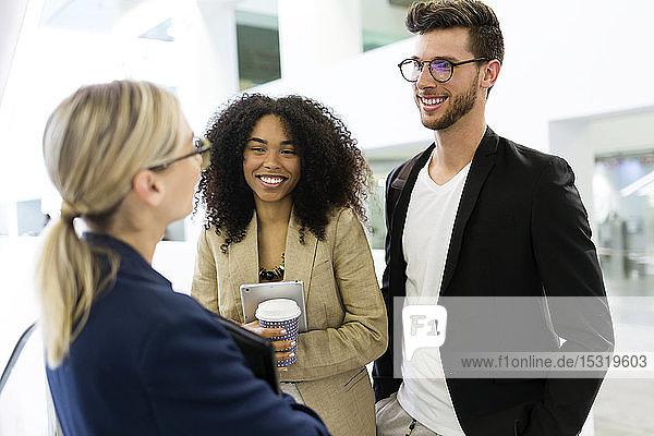 Junge Geschäftsleute im Gespräch auf dem Flur