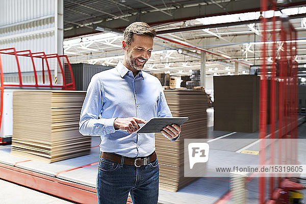 Smiling businessman using tablet in a factory