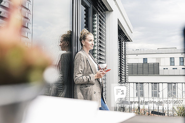 Businesswoman with cell phone and coffee cup standing on roof terrace