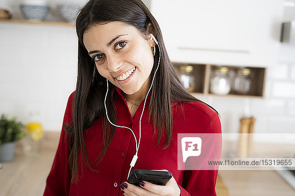 Portrait of smiling young woman with earphones and smartphone
