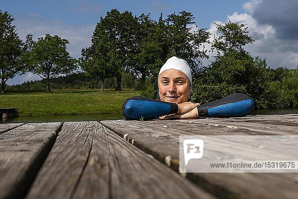 Porträt einer jungen Triathletin  die auf einem Steg an einem See lehnt