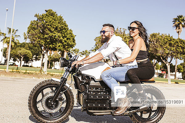 Happy couple on motorbike in summer