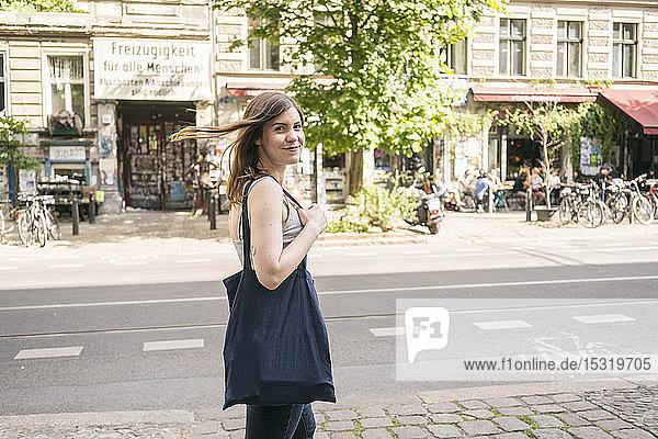Porträt einer lächelnden jungen Frau auf der Straße in der Stadt