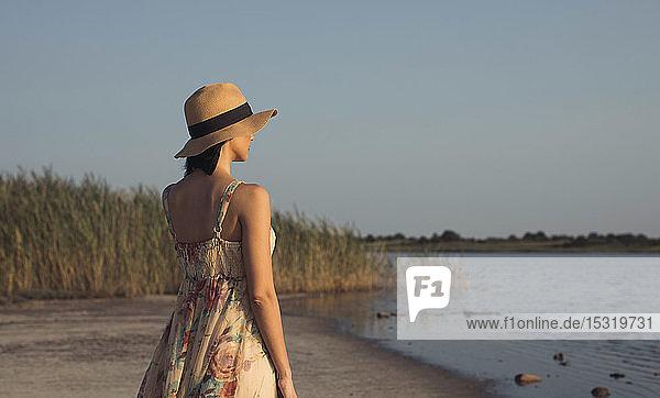 Frau im Sommerkleid  die an einem See steht