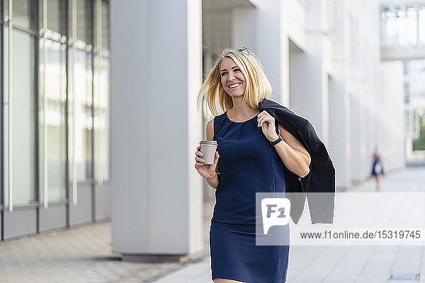 Portrait of smiling blond businesswoman with coffee to go wearing blue summer dress