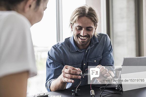 Lächelnder junger Mann und lächelnde Frau  die im Büro an Computerausrüstung arbeiten
