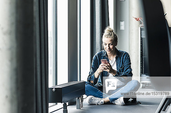 Businesswoman sitting on the floor in office using cell phone