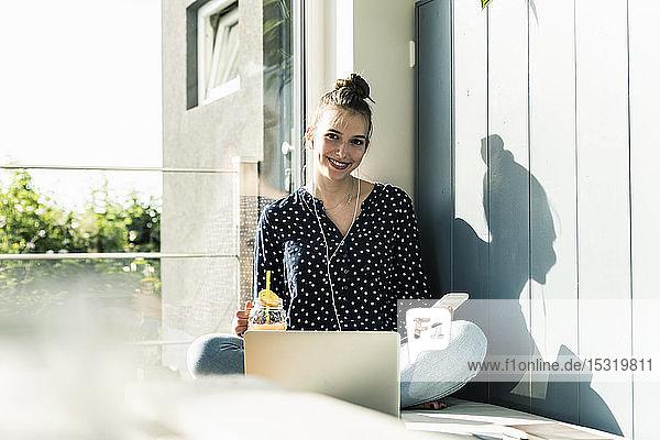 Lächelnde junge Frau mit Laptop  Handy und gesundem Getränk zu Hause