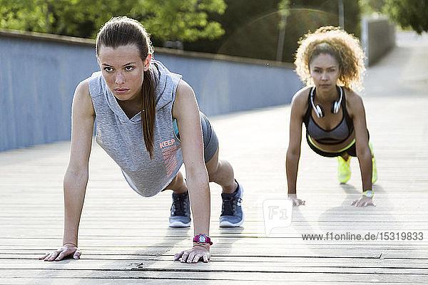 Two sporty young women doing push-ups on a bridge