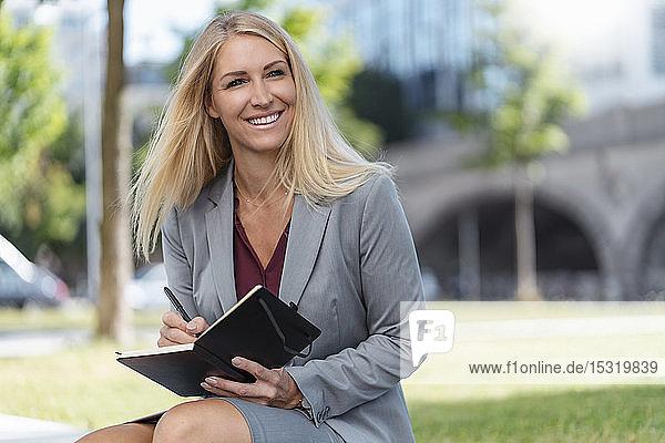 Porträt einer lächelnden blonden Geschäftsfrau mit Notizbuch  die im Freien sitzt
