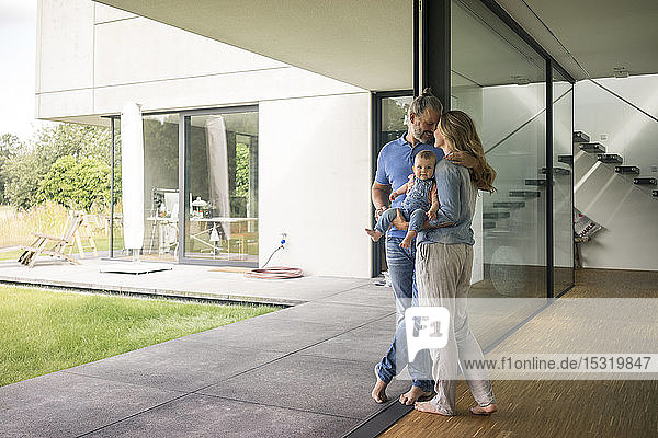 Dreiköpfige Familie  die zu Hause am Fenster steht