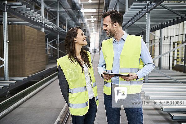 Kollegen mit reflektierenden Westen mit Tablette in der Fabrik