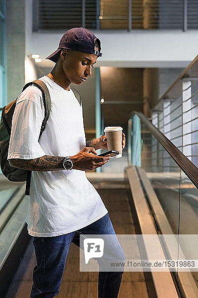 Young man with backpack and coffee to go standing on escalator looking at cell phone