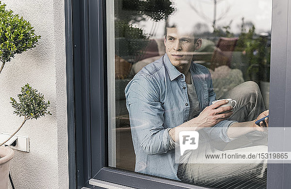 Man sitting st the window  drinking coffee