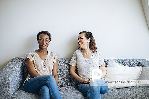 Two smiling women sitting on couch at home