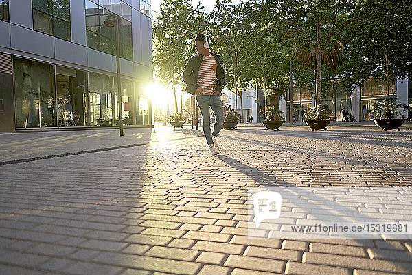 Young man with headphones walking on street at backlight