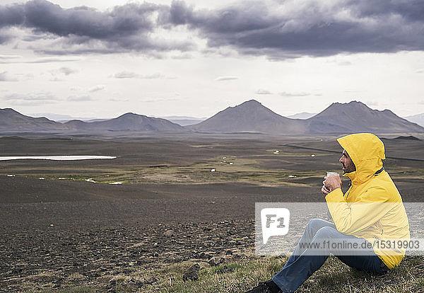 Erwachsener Mann macht eine Pause  trinkt Kaffee  Island