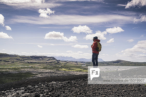 Hiker in Vesturland  Iceland  standing and looking at landscape