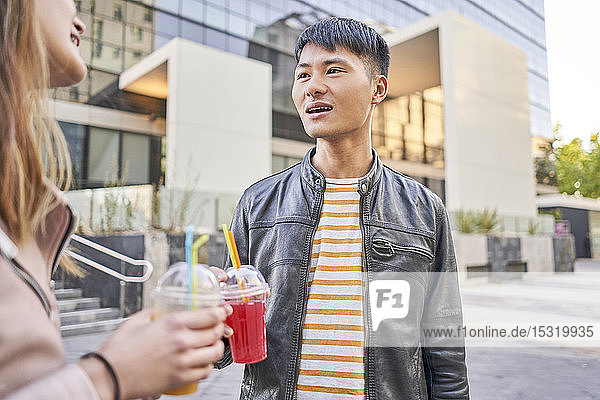 Porträt eines jungen Mannes mit Erfrischungsgetränk im Gespräch mit seiner Freundin
