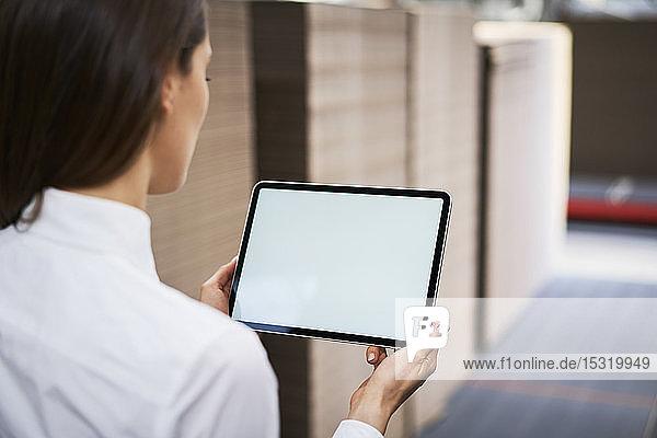Nahaufnahme einer Frau mit Tablette in einem Fabriklager
