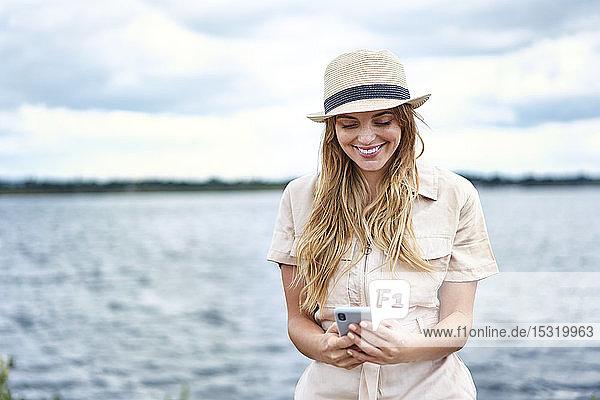 Glückliche Frau beim Handy-Checken am Seeufer