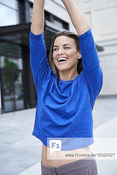 Porträt einer glücklichen attraktiven brünetten Frau im blauen Top in der Stadt