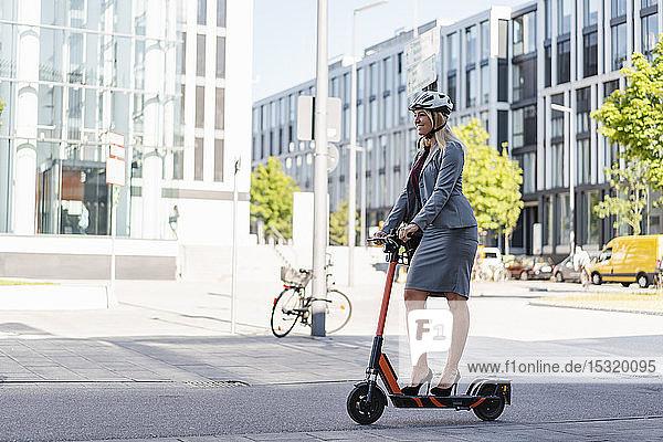 Lächelnde Geschäftsfrau in Stöckelschuhen mit Elektroroller auf der Straße
