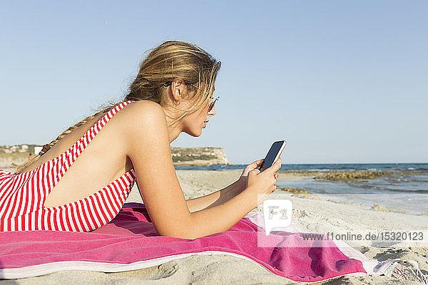 Junge Frau mit Smartphone am Strand