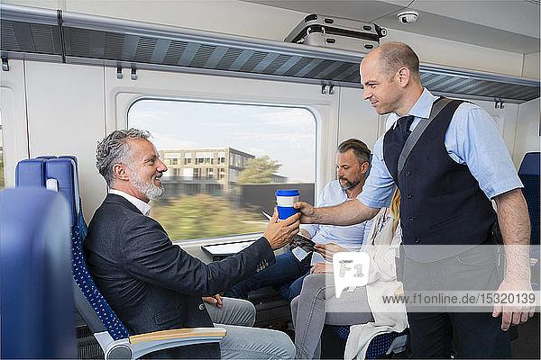 Schaffner  der einem Zugpassagier Kaffee serviert