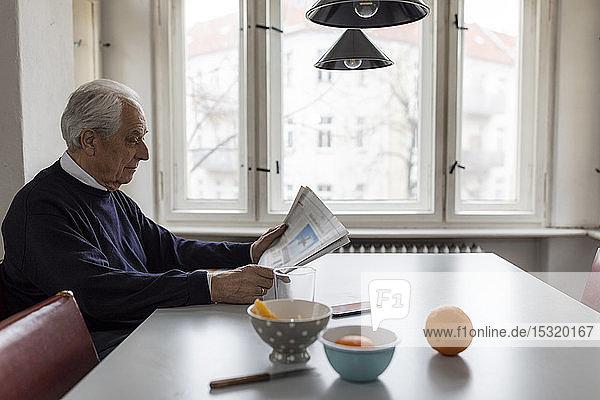 Älterer Mann liest zu Hause Zeitung