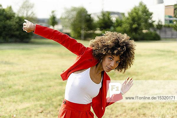 Porträt einer sich bewegenden jungen Frau in modischem roten Hosenanzug und weißem Oberteil
